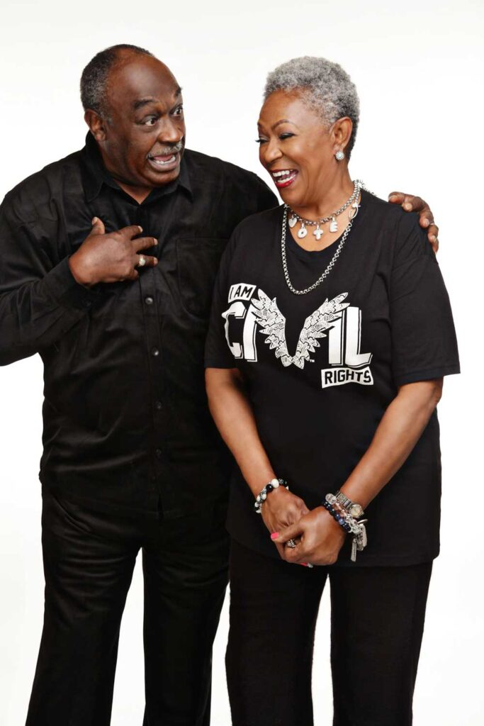 Paulette and Curtis Roby, laughing together, dressed in black.