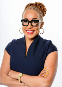 smiling black woman wearing black glasses in a dark blue top with yellow fingernail polish