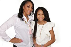 Beautiful smiling women with daughter both wearing white tops and fun necklaces