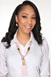 Smiling woman in white top on white background wearing a pink long beaded necklace with a tassel