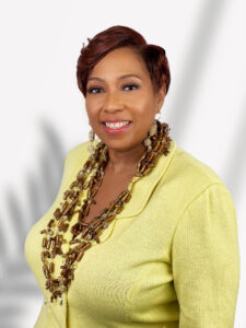 Charletta Wilson Jacks is a progressive leader in yellow suit and coral layered necklaces
